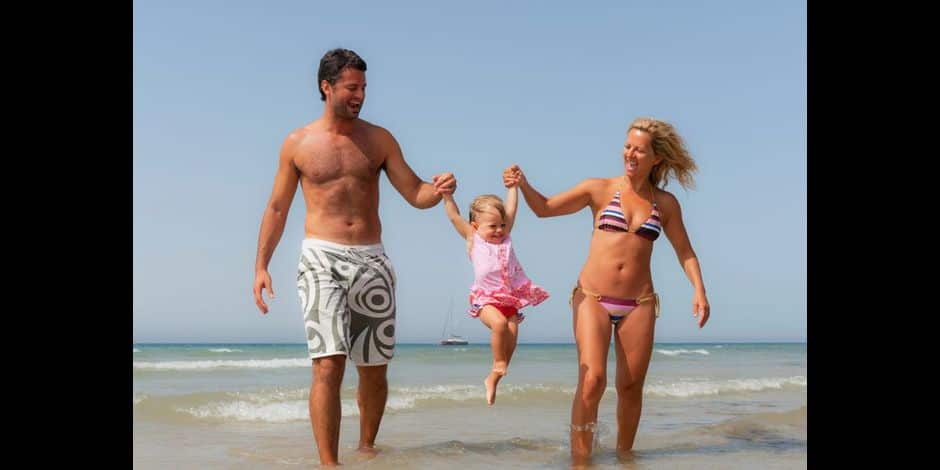 A Mother And Father Playing With Their Young Daughter On The Beach; Tarifa Cadiz Andalusia Spain