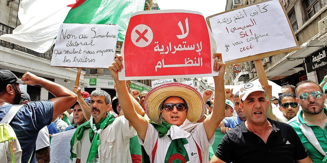 Algerian protesters hold posters as they demonstrate in Algiers on August 2, 2019, for the 24th consecutive Friday against the ruling class amid an ongoing political crisis in the country. (Photo by - / AFP)