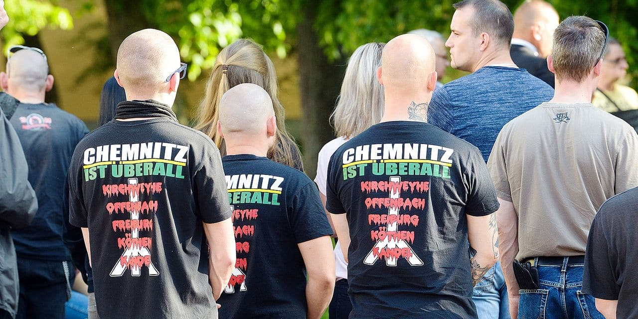 """19 May 2019, Saxony-Anhalt, Köthen: Three participants of a demonstration of the right-wing scene are standing with their shirts with the inscription """"Chemnitz is everywhere"""" in the city centre. After the verdict in the trial for the death of a young man, rights and counter-demonstrators took to the streets in Köthen. About 180 participants of a right-wing spontaneous demonstration went on Sunday towards the scene of the crime where a 22-year-old man had died in September. Photo: Heiko Rebsch/dpa Reporters / DPA"""