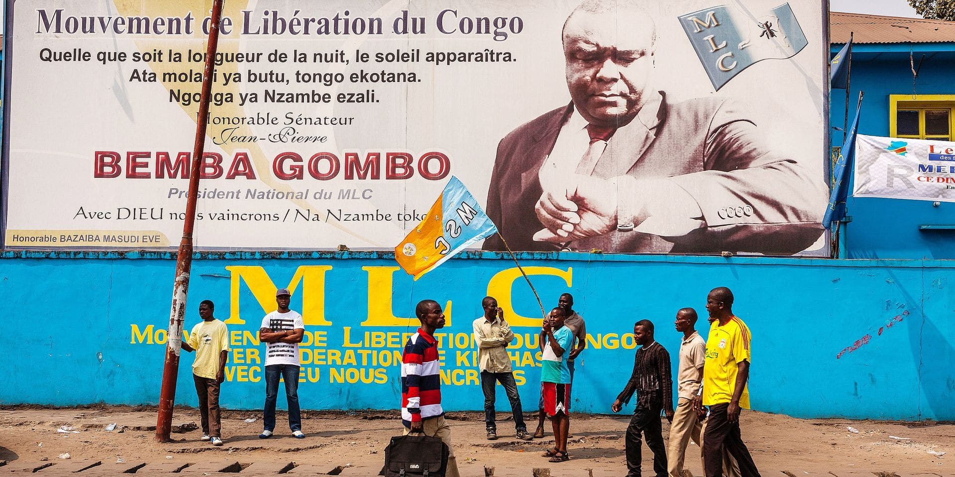 """Opposition supporters gather under a billboard of Movement for the Liberation of the Congo (MLC) leader Jean-Pierre Bemba Gombo before a rally organised by political opposition parties in Kinshasa on July 31, 2016. Congo's veteran opposition chief Etienne Tshisekedi on July 31 called for elections to be held this year and for President Joseph Kabila to step down as scheduled on December 20. Tensions have been growing in the mineral-rich but troubled state over fears that Kabila, in power since 2001, may try to extend his rule with a third term, beyond the constitutional maximum of two. Speaking at a rally in Kinshasa, Tshisekedi warned him not to try, saying it would be """"high treason"""" if the electoral process were not launched on schedule in September. / AFP PHOTO / Eduardo Soteras"""