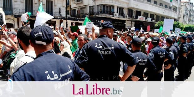 Algerian policemen surround protesters during a demonstration in Algiers on July 12, 2019, in the latest in weeks of rallies against the ruling class amid an ongoing political crisis in the country. - Algeria has been rocked by months of demonstrations, forcing longtime president Abdelaziz Bouteflika to step down in April. Protesters have continued to take to the streets, demanding that regime insiders leave office and independent institutions be established ahead of eventual elections. (Photo by RYAD KRAMDI / AFP)