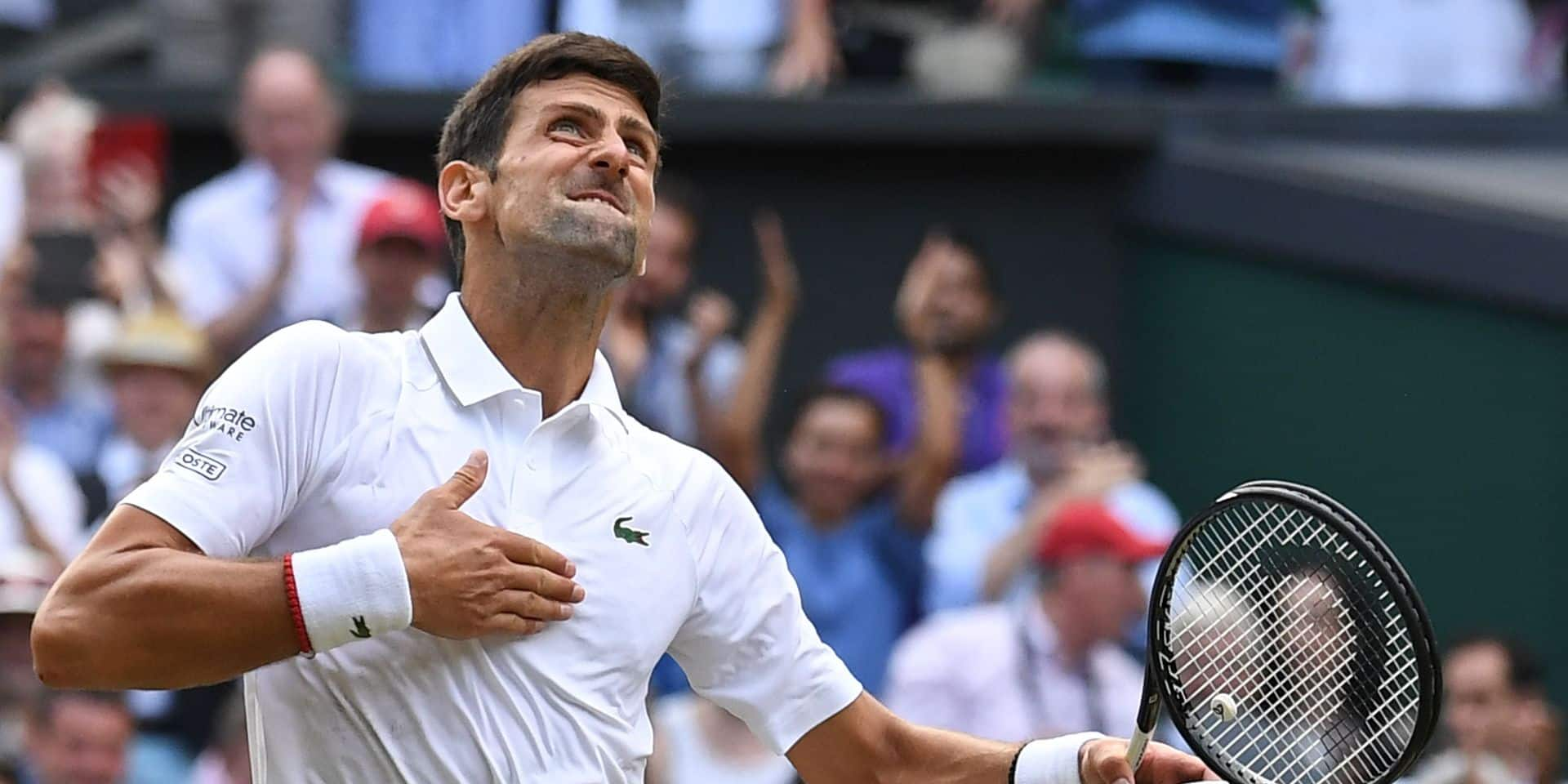 TOPSHOT - Serbia's Novak Djokovic celebrates beating Switzerland's Roger Federer during their men's singles final on day thirteen of the 2019 Wimbledon Championships at The All England Lawn Tennis Club in Wimbledon, southwest London, on July 14, 2019. (Photo by Ben STANSALL / AFP) / RESTRICTED TO EDITORIAL USE