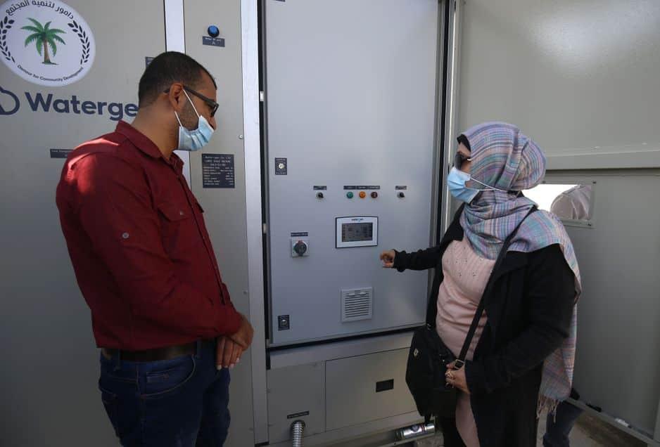 L'ingénieur palestinienne Nadia Tubail (à droite) vérifie un générateur d'eau alimenté par l'énergie solaire qui extrait l'eau potable directement de l'air.