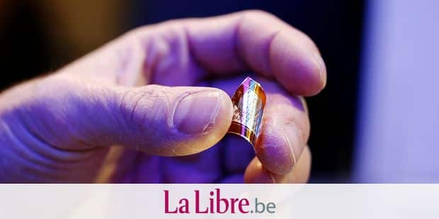 A hosts holds a graphene chip used for Internet of Things (IoT) of the German RWTH Aachen University presented at the Mobile World Congress (MWC), the world's biggest mobile fair, on February 27, 2018 in Barcelona. The Mobile World Congress is held in Barcelona from February 26 to March 1. / AFP PHOTO / Pau Barrena