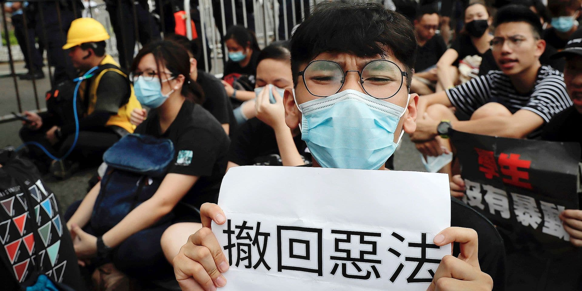 Protesters gather behind police line calling Hong Kong Chief Executive Carrie Lam to step down as they continue protest against the unpopular extradition bill near the Legislative Council in Hong Kong, Monday, June 17, 2019. A member of Hong Kong's Executive Council says the city's leader plans to apologize again over her handling of a highly unpopular extradition bill. (AP Photo/Kin Cheung)