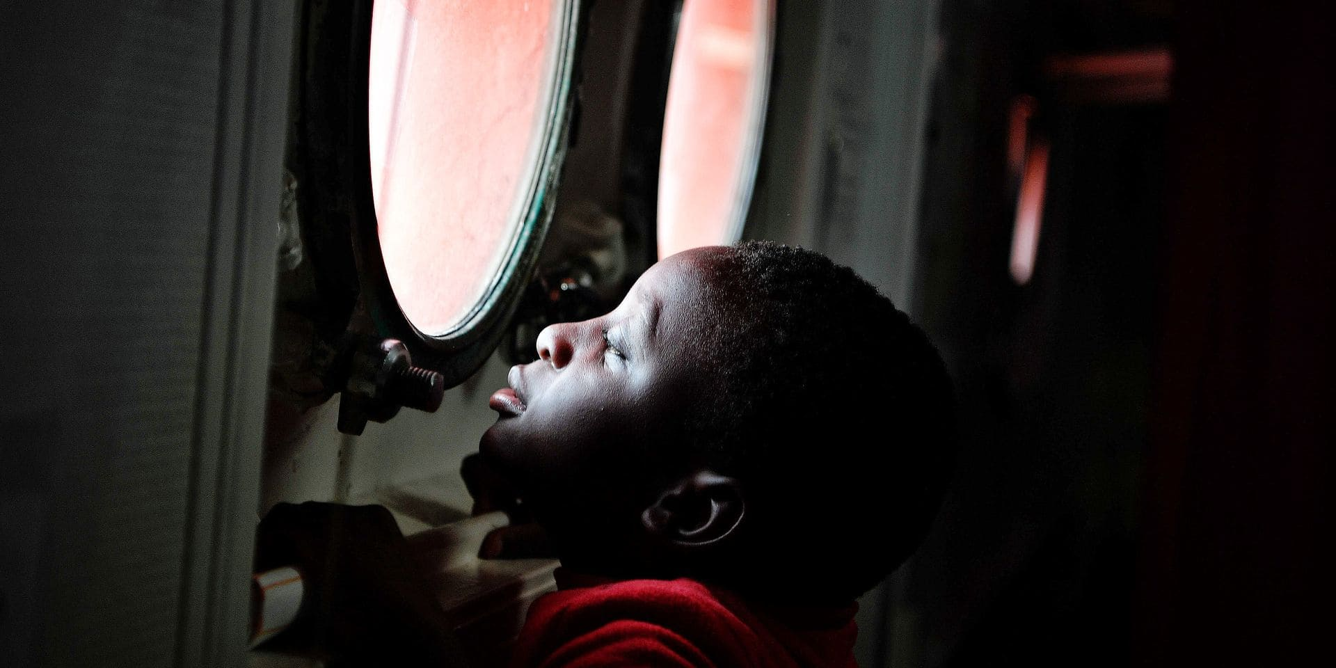 A child tries to peer out from the porthole of the MV Aquarius upon its arrival at the Sicilian port of Messina, on May 14, 2018. On May 12, 2018, 73 migrants of various nationalities, including women and children, were rescued by MV Aquarius a rescue vessel chartered by SOS-Mediterranee and Doctors Without Borders (MSF). / AFP PHOTO / LOUISA GOULIAMAKI