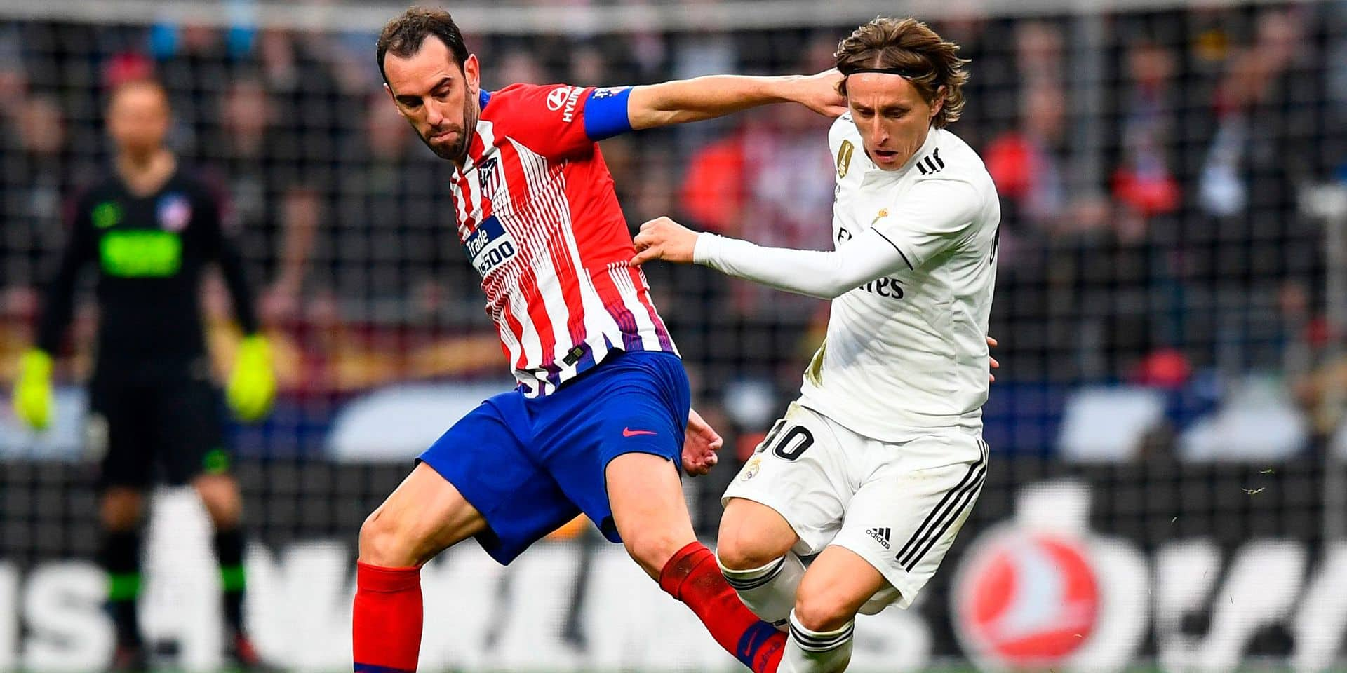 Atletico Madrid's Uruguayan defender Diego Godin (L) challenges Real Madrid's Croatian midfielder Luka Modric during the Spanish league football match between Club Atletico de Madrid and Real Madrid CF at the Wanda Metropolitano stadium in Madrid on February 9, 2019. (Photo by GABRIEL BOUYS / AFP)