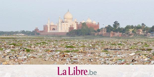 In this Friday, May 11, 2018 photo, garbage covers the area by the Yamuna river near the Taj Mahal in Agra, India. Built by Mogul Emperor Shah Jahan for his favorite wife in the north Indian city of Agra, the Taj Mahal has been losing its sheen for years. The shining white monument to love is turning a little green and yellow because of air pollution and swarms of insects. (AP Photo/Pawan Sharma)