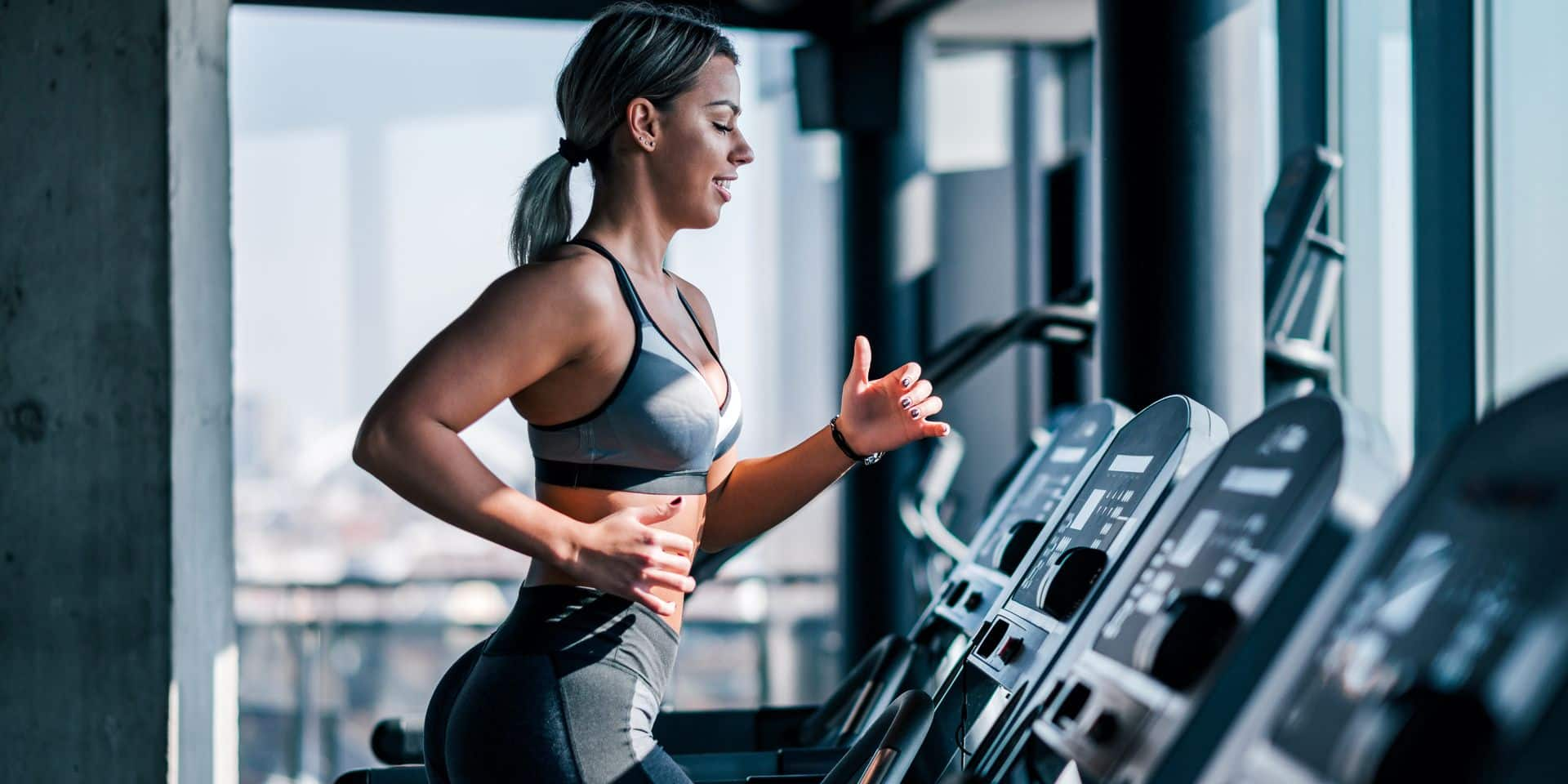 Side,View,Of,Beautiful,Muscular,Woman,Running,On,Treadmill.