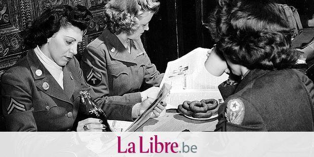 """Deuxieme (Seconde) guerre mondiale (1939-1945) - World War II (WWII or WW2) : Bruxelles (Belgique) 25 aout 1945 : Lors d'une permission, ces trois caporaux WAC (Women Army Corps) de l'US Army se restaurent au Club Ardennais de la Croix-rouge avec des doughnuts (beignet), du Coca-Cola, du cafe et la lecture du journal """"Stars and Stripes"""" ©Usis-Dite/Leemage Reporters / Leemage"""