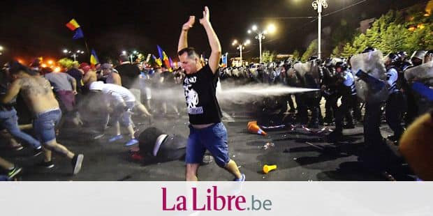 "Romanian anti riot police clash with protesters during a demonstration in front of the Romanian Government headquarters in Bucharest August 10, 2018, to protest against the government. - Romanian police used tear gas and pepper spray to quell anti-corruption protesters in Bucharest on August 10, 2018, as tens of thousands called on the leftwing government to resign. Local media said between 30,000 to 50,000 people turned out for the protest, included many Romanian expatriates who returned home especially to show their anger at the levels of official corruption. The crowd chanted ""resign"" and ""thieves"" as they assembled in a central square outside the main government building. (Photo by Daniel MIHAILESCU / AFP)"