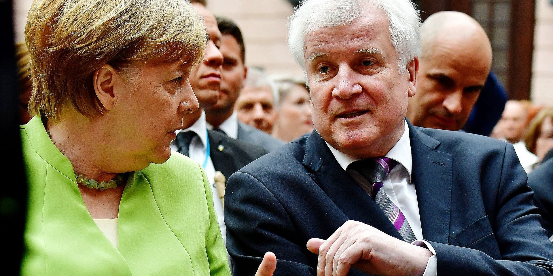 Chancellor Angela Merkel sits next to German Interior Minister Horst Seehofer as they attend a ceremony commemorating the victims of displacement on Germany's refugee day, at the German Histic Museum (DHM) in Berlin on June 20, 2018. / AFP PHOTO / Tobias SCHWARZ