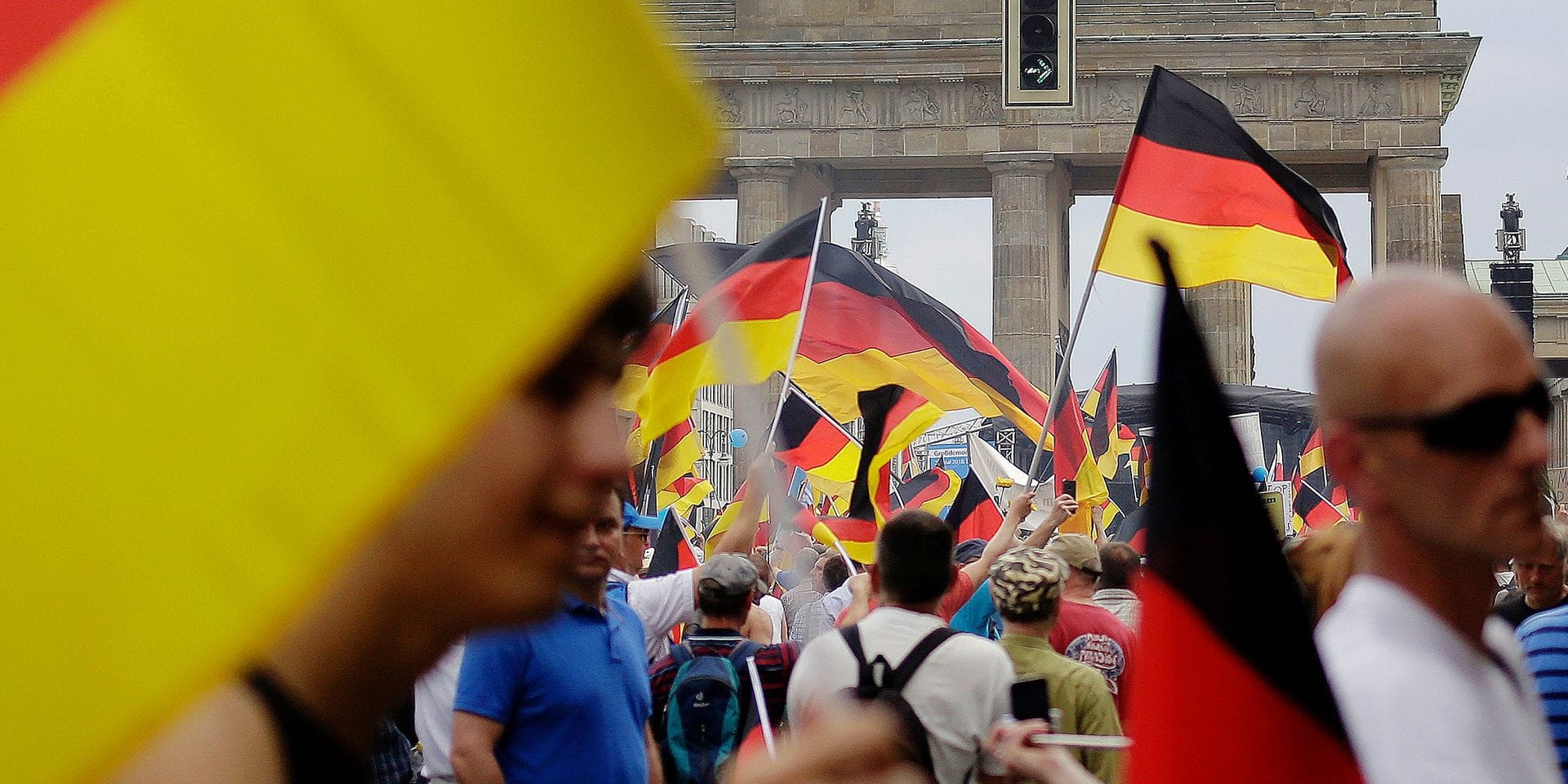 AfD supporters wave flags in front of the Brandenburg Gate in Berlin, Germany, Sunday, May 27, 2018. The AfD that swept into Parliament last year on a wave of anti-migrant sentiment is staging a march Sunday through the heart of Berlin to protest against the government. (AP Photo/Markus Schreiber)