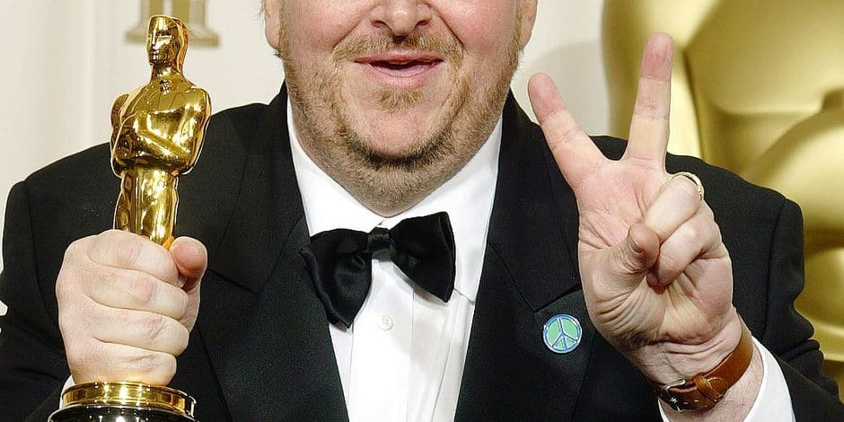 """Comedian and documentary-maker Michael Moore flashes the V-sign after winning Best Documentary Feature for """"Bowling For Columbine"""" at the 75th Academy Awards in Hollywood, California, 23 March, 2003. AFP PHOTO/Lee CELANO / AFP PHOTO / LEE CELANO"""