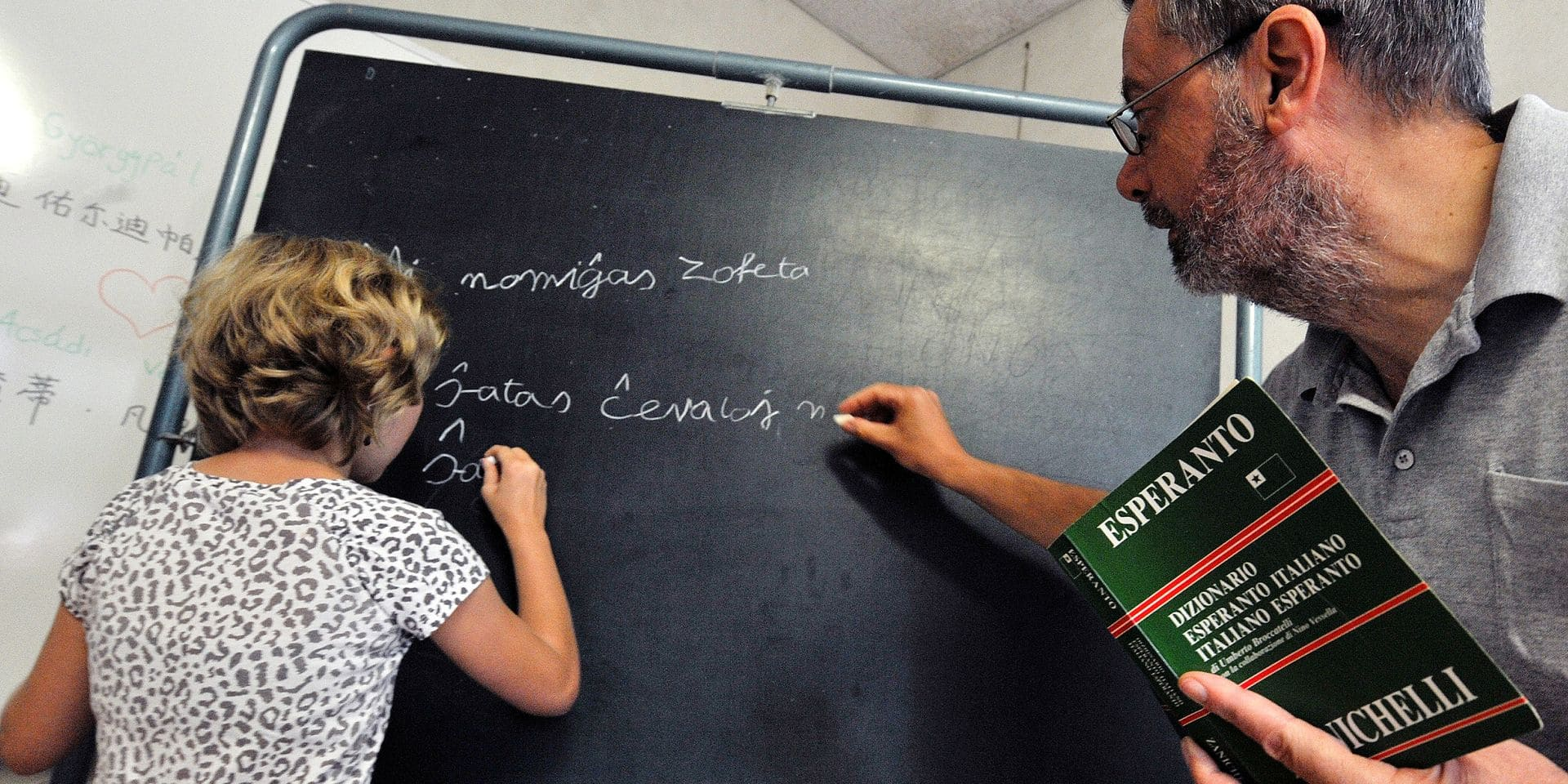 TO GO WITH AFP STORY BY PHILIPPE SCHWAB A girl writes on a blackboard during an Esperanto lesson on August 8, 2013 at the Chateau de Gresillon in Saint-Martin-d'Arce, western France. Esperanto is an artificial international language, created in 1887 by Polish oculist Lazarus Ludwig Zamenhof, and based as far as possible on words common to the chief European languages. AFP PHOTO / FRANK PERRY / AFP PHOTO / FRANK PERRY