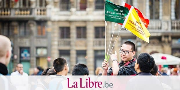20130502 - BRUSSELS, BELGIUM: Illustration picture shows a Chinese guide holding flags as tourists visit the Brussels Grand Place on Thursday 02 May 2013. BELGA PHOTO SISKA GREMMELPREZ