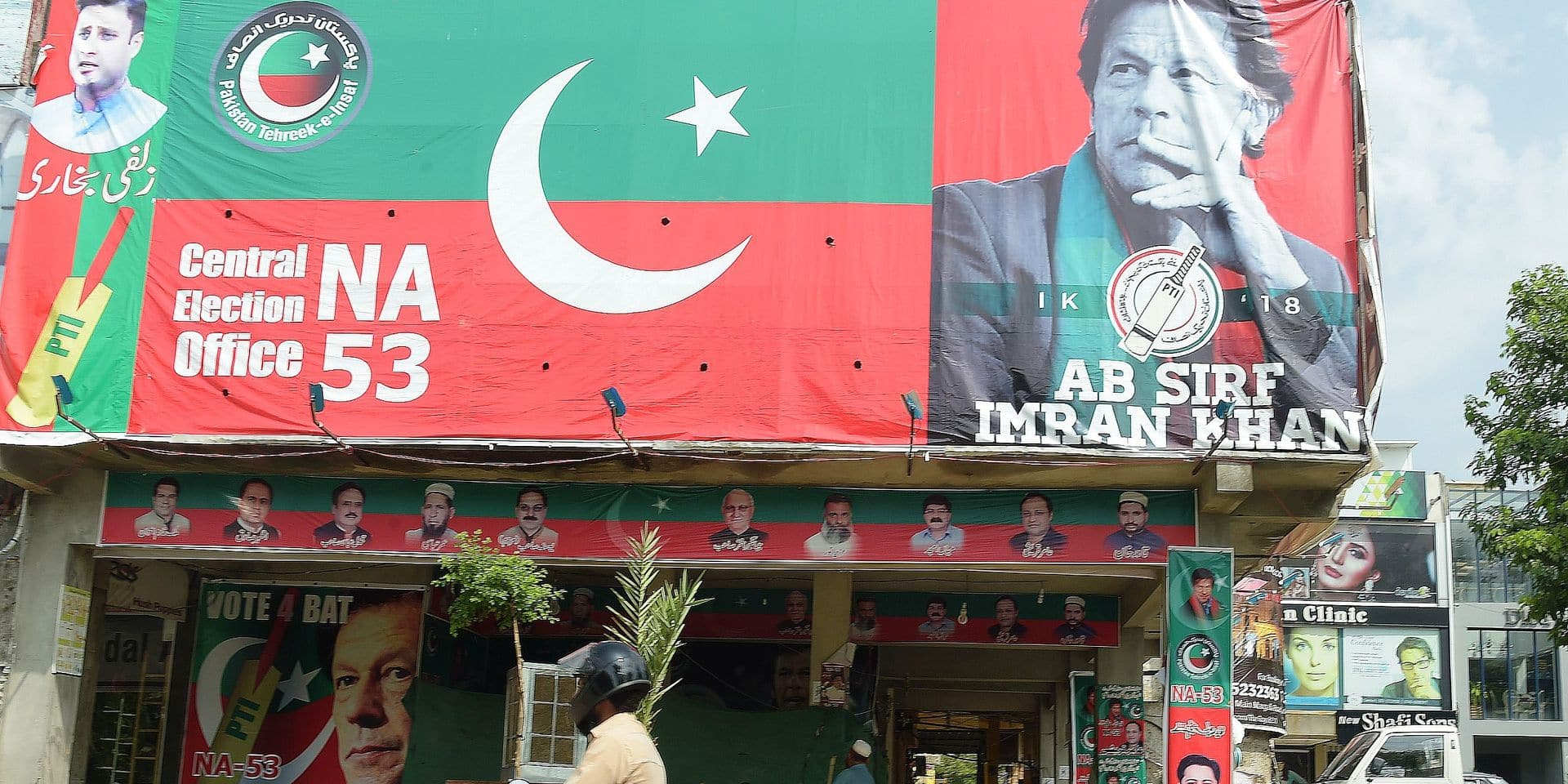 "TOPSHOT - A Pakistani motorcyclist rides past a billboard featuring an image of Pakistan's cricketer-turned politician Imran Khan, head of the Pakistan Tehreek-e-Insaf (Movement for Justice) party, a day after the general election in Islamabad on July 26, 2018. Pakistan woke to electoral chaos on July 26 with the outgoing ruling party denouncing ""blatant rigging"" in the pivotal general election and rejecting unofficial, partial results suggesting victory for former cricket champion Imran Khan. / AFP PHOTO / AAMIR QURESHI"
