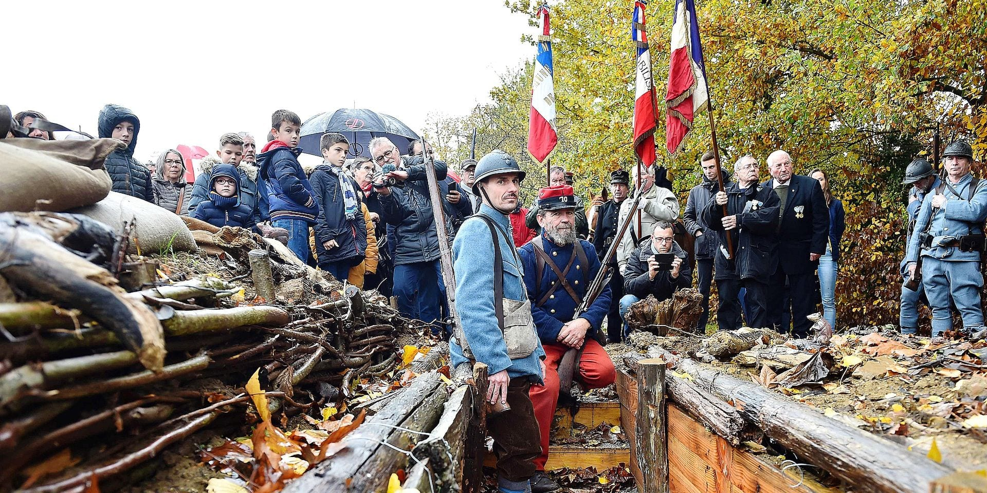 Inhabitants of Souille and La Guierche and history enthusiast, dressed with vintage army uniforms of Poilu (French soldier in World War I), stand guard in a reconstructed trench of the WWI, as they take part in a ceremony to inaugurate the trench on November 11, 2018, as part of the commemorations marking the 100th anniversary of the 11 November 1918 armistice, ending World War I, in La Guierche, northwestern France. - The trench, dug next to the village hall, by young people, as part of citizens' days, is intended to be preserved and to serve as a memorial site. (Photo by JEAN-FRANCOIS MONIER / AFP)